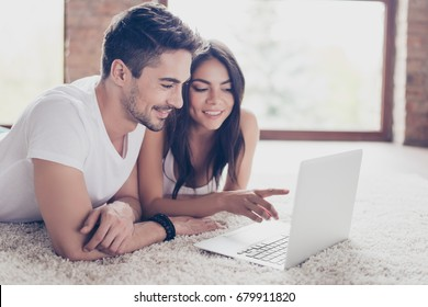 Beautiful latino mulatto lovers are browsing info on laptop and discussing it, lying on the floor on comfortable carpet at home. They are smiling, so relaxed
