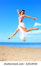 Beautiful latino woman jumping by the sea in Greece