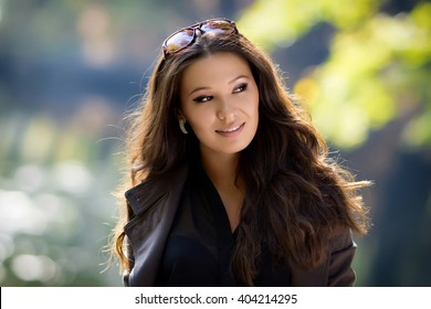 Beautiful latinonos woman in casual wear  walking on the park. Fashionable girl 