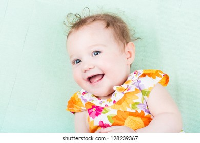 Beautiful laughing baby girl in a colorful floral dress