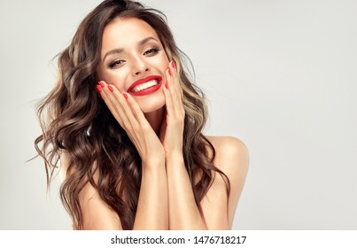 Beautiful laughing brunette model  girl  with long curly  hair . Smiling  woman hairstyle wavy curls . Red  lips and  nails manicure .    Fashion , beauty and make up portrait