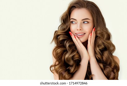Beautiful laughing brunette model  girl  with long curly  hair . Smiling  woman hairstyle wavy curls . Red  nails manicure .    Fashion , beauty and makeup portrait