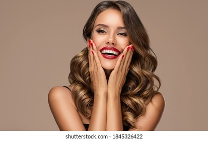 Beautiful laughing brunette model  girl  with long curly  hair . Smiling  woman hairstyle wavy curls . Red  lips and  nails manicure .    Fashion , beauty and make up portrait - Shutterstock ID 1845326422