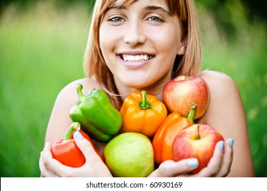 Beautiful laughing girl with apples and sweet pepper, on green summer background.