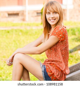 Beautiful laughing girl in red dress sits on wooden ladder.
