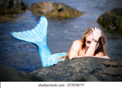 Beautiful  laughing mermaid having rest on the ocean rocks