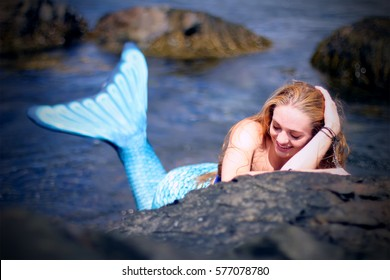 Beautiful  laughing mermaid having rest on the ocean rocks. Spirit of the ocean.