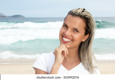 Beautiful laughing woman with blonde hair at beach with blue sky, ocean and waves in the background