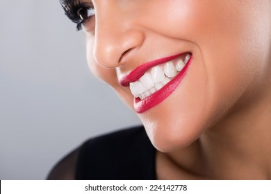 Beautiful laughing woman with red lips and white teeth, closeup, on grey background, studio shot