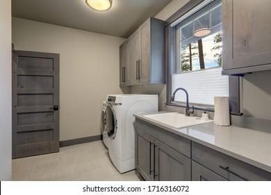 Hermosa lavandería con puertas de madera y lavadora y secadora blancas.