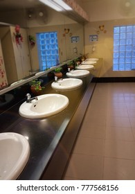 Beautiful lavatory blurry images have white sink on black counter bright mirror and blue glass window have sunlight