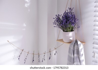 Beautiful lavender flowers and towel on hanging shelf indoors. Space for text