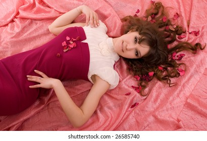The beautiful laying girl with petals in hair