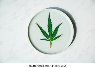 Beautiful leaf hemp on a round plate. The concept of growing cannabis for oil, medical purposes.