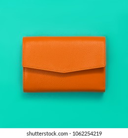Beautiful leather wallet, rich orange, laying on a turquoise bright paper background, mock up