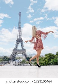 A beautiful leggy blonde in a short pink dress sits on a Trocadero against the backdrop of the Eiffel Tower in Paris.