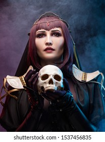 A beautiful leggy busty cosplay girl wearing an erotic leather costume poses holding fake human skull in her hands on a dark background in  theatrical smoke