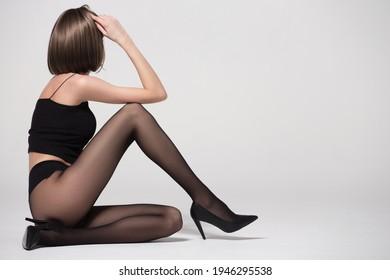 Schöne Leggy-Frau in schwarzen Strumpfhosen und High-Ferel-Schuhen