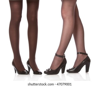 Beautiful legs in black shoes. Isolated on white