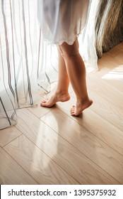beautiful legs of the bride in a white nightie