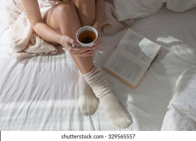 Beautiful Legs close-up in Bed,  Woman with a Cup of refreshing Tea, Warm Knitted Socks and a Plaid dress on a Girl, she basked in the Bed and Reading a Book, the sun's rays shine into the Bedroom