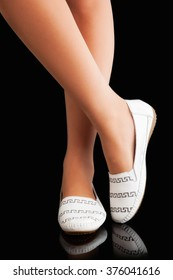 beautiful legs in a comfortable elegant shoes on a black background