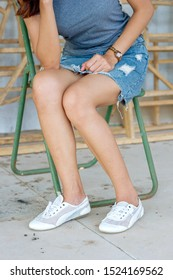 The beautiful legs of a girl sitting on an iron chair