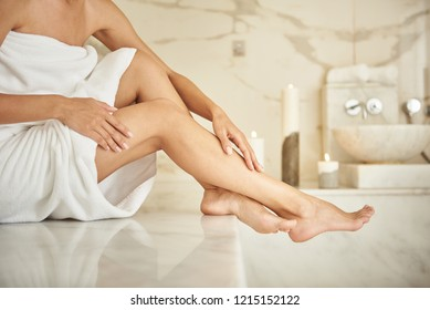 Beautiful legs. Pretty lady wearing white towel and softly touching her legs while being in the Turkish bath