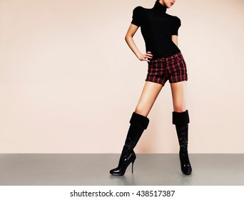 Beautiful legs woman with black leather boots isolated on light brown background. Fall, autumn winter fashion.