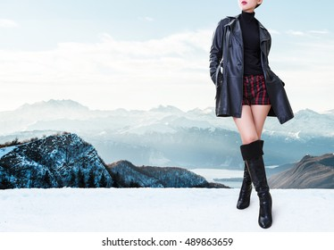Beautiful legs woman with black leather coat jacket,high heels boots and shorts standing in the winter mountain. Italy Swiss Alps mountain.