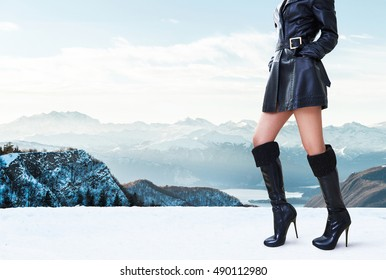 Beautiful legs woman with black leather coat jacket,high heels boots standing in the winter mountain. Italy Swiss Alps mountain.