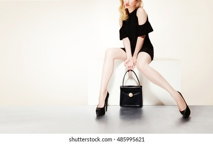Beautiful legs woman with black purse hand bag with heels shoes sitting on the bench. isolated on white background with copy space.