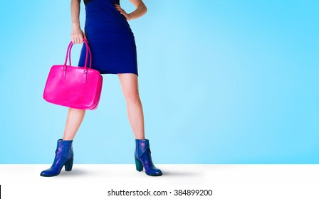 Beautiful legs woman with blue boots and pink bag. Isolated on blue with copy space. Fashion shopping image.