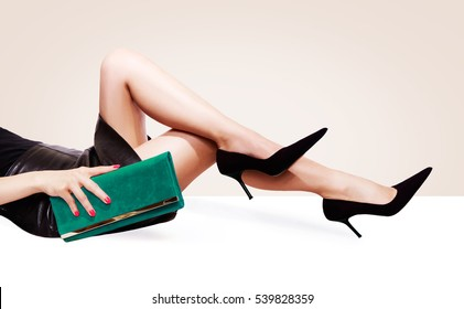 Beautiful legs woman with green purse and black heels shoes sitting on the white table. Copy space on the light beige background.