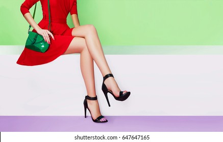 Beautiful legs woman with red dress, green purse and black heels shoes sitting on the white bench. Colorful fashion image with copyspace.