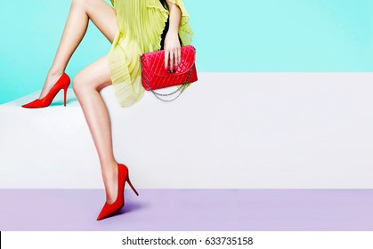 Beautiful legs woman with red heels shoes and purse handbag sitting on the white bench
