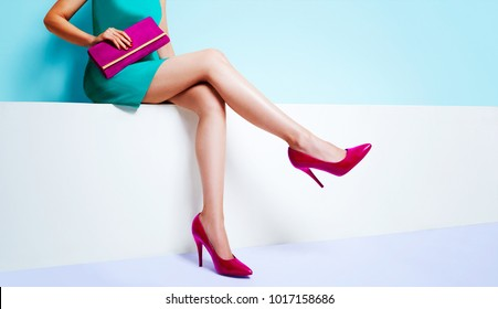 Beautiful legs woman sitting on the bench. With red pink purse and high heel shoes.