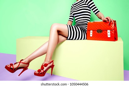 Beautiful legs woman sitting on the bench. With orange bag and red high heel shoes.