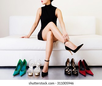 Beautiful legs. Woman trying many shoes. choosing.