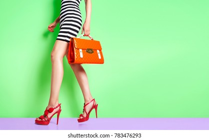 Beautiful legs woman walking with red heels and orange bag. isolated on green wall.