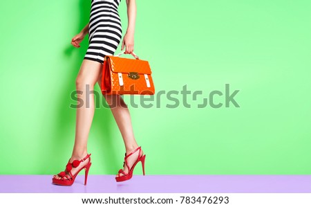 632d10faea1d Beautiful legs woman walking with red heels and orange bag. isolated on  green wall.
