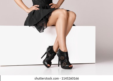 Beautiful legs woman wearing black dress and high heels shoes sitting on white bench.