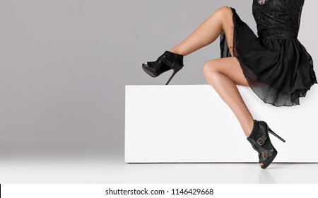 Beautiful legs woman wearing black dress and high heels shoes sitting on white bench. with copyspace.