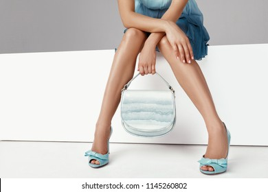 Beautiful legs woman wearing blue dress with blue purse hand bag, high heels shoes sitting on white bench.