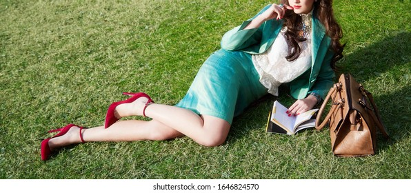 Beautiful legs woman wearing red shoes heels and handbag. Reading book on the grass