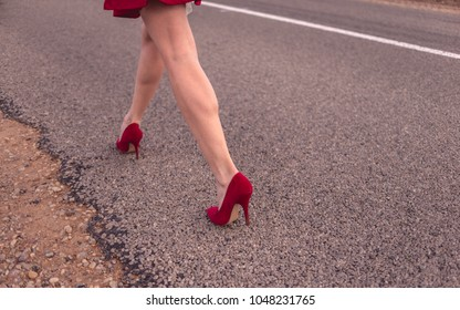 Beautiful legs of a woman wearing a short skirt and red shoes and striding down the roadway