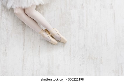 Beautiful legs of young ballerina in pointe shoes at white wooden floor background, top view from above with copy space. Ballet practice. Beautiful slim graceful feet of ballet dancer.