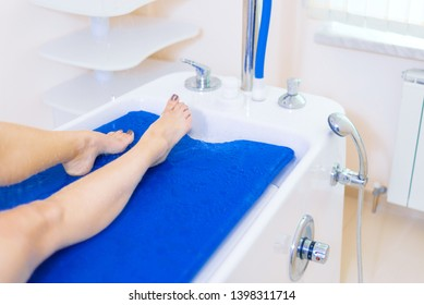 beautiful legs of a young girl under a stream of water. Vichy Shower Massage Therapy. body care concept