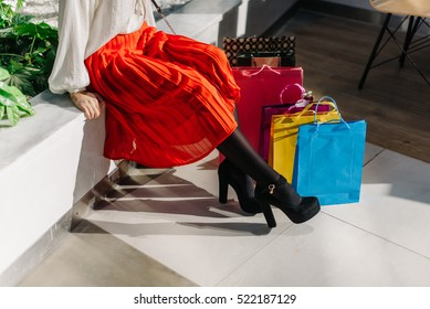 Beautiful legs of young pretty woman in midi red skirt, white shirt and shoes on high heels after shopping in big mall sitting on the bench. Many colorful shopping bags near.