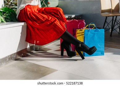 Beautiful legs of young pretty woman in midi red skirt, white shirt and shoes on high heels after shopping in big mall sitting on the bench. Many shopping bags near.